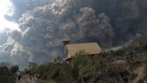 A giant cloud of hot volcanic ash clouds engulfs villages in Karo district during the eruption of Mount Sinabung volcano located in Indonesia's Sumatra island on February 1