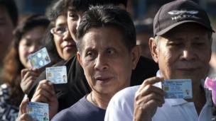 Thai voters show their ID cards as they queue to cast their ballot at a polling station in Bangkok