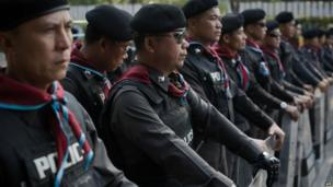 Thai police officers secure and block a street leading to a polling station occupied by Thai anti-government protesters