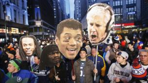 Fans hold up posters of Seattle Seahawks head coach Pete Carroll, quarterback Russell Wilson, running back Marshawn Lynch, and cornerback Richard Sherman.