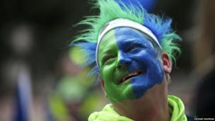 fan with face painted blue and green