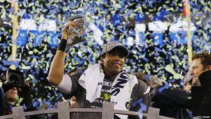 Quarterback Russell Wilson #3 of the Seattle Seahawks celebrates with the Vince Lombardi Trophy after their 43-8 victory over the Denver Broncos during Super Bowl XLVIII