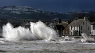 The coast road at Carnlough in Co Antrim, at high tide, as waves break over the front.