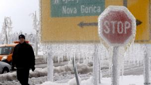 A man walks next to ice-covered road signs in Postojna February 3, 2014