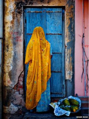 A woman dressed in traditional garb returns home from a street market
