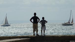 Craig Pillay in Port Elizabeth, South Africa with his son in front of the sea