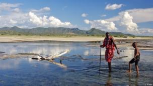 Maasai helping a young boy in Kenya