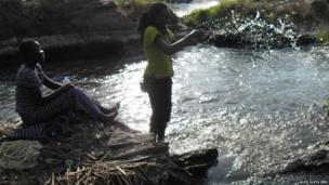 Alice Oleya Jino and friend splashing in the Fulla Falls in South Sudan