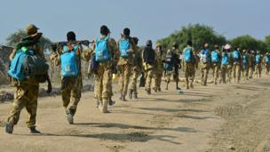 South Sudan soldiers walking along a road with backpacks, many of the with the Unicef logo, on a dirt road in Jonglei state, South Sudan - Friday 31 January 2014