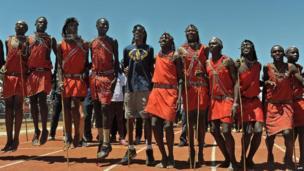 Mo Farah in a blue T-shirt amidst dancing Maasai warriors at the Lorna Kiplagat Sports Academy in Iten, Kenya - Saturday 1 February 2014