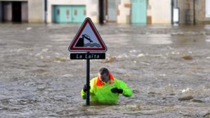 A man checks a signpost in a street flooded by the coastal river Laita in the city centre of Quimperle, western France