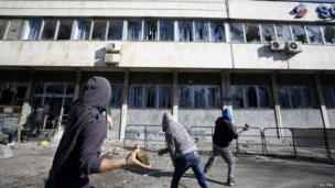 Protesters are throwing rocks at a government building in Tuzla (7 February 2014)