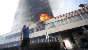 Man stands outside a burning government building in Tuzla (7 February 2014)