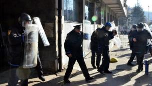 Police hold up shields outside a government building in Tuzla (7 February 2014)