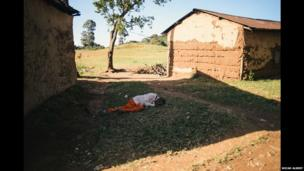 A man who has passed out in a village in western Kenya