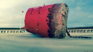 Buoy which has been washed up on the beach by the storms. Photo: Chris Parkinson