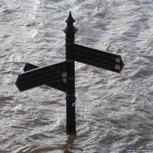 Signpost surrounded by flood water from the River Severn. Photo: Simon Shearburn