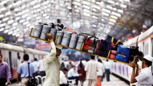 Two ports carry a tray of tiffin boxes onto a train in Mumbai