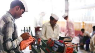 Dabbawalas sort the tins into groups depending on their destination.