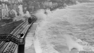 Waves crash over another train travelling through Dawlish