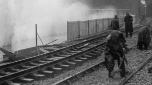 Railway workers clear rubble on the line at Dawlish