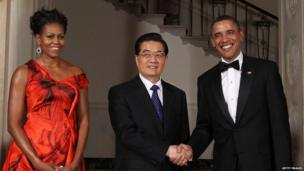 President Barack Obama and Chinese President Hu Jintao shake hands and pose with First Lady Michelle Obama outside the White House on 19 January 2011