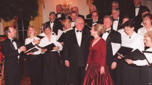 German Chancellor Helmut Kohl, President Bill Clinton, and First Lady Hillary Clinton sing with the Washington Saengerbund German chorus in 1995.