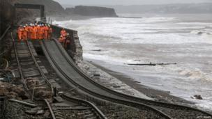 Railway workers inspect the main Exeter to Plymouth railway line that has been closed due to parts of it being washed away by the sea at Dawlish
