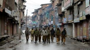 Indian policemen patrol alongside shuttered shops in Srinagar