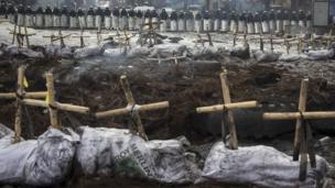 Riot police stand behind crosses installed by anti-government protesters in memory of the people who have died or disappeared during clashes in Ukraine, near the barricades in Kiev February 11, 2014.