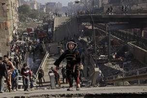 Residents stand on a bridge which collapsed in el-Marg, a suburb northeast of Cairo, Egypt, Tuesday, Feb. 11, 2014.