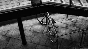 A bicycle tied under the stairs