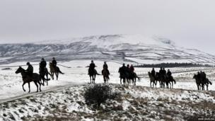 Riders out on their horses on the hilltops near Leyburn in the snow