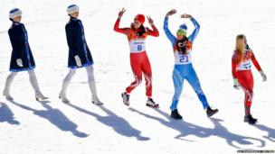 Joint winners Switzerland's Gisin and Slovenia's Maze walk out ahead of flower ceremony for the women's alpine skiing downhill race at the 2014 Sochi Winter Olympics