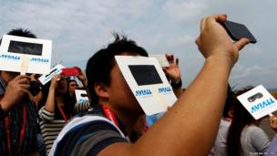 Spectators shield their eyes from the sun with cardboard visors as they watch aerial displays at the Singapore Airshow