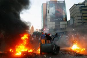 Demonstrators make a barricade of burning rubbish in Caracas