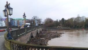 Debris trapped by floodwater against a bridge in the centre of Worcester