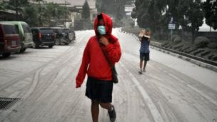 Indonesian students walk on a street covered with volcanic ash following an eruption of Mount Kelud, in Yogyakarta, Indonesia, 14 February 2014