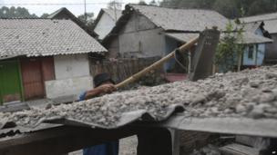 A man cleans a roof covered with volcanic ash from an eruption of Mount Kelud at Mbladak village in Blitar, Indonesia, 14 February 2014