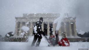 A Park Service employee clears snow in front of the Lincoln Memorial in Washington