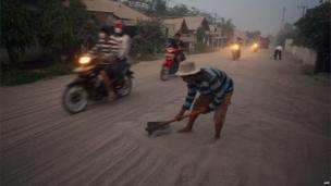 A resident clears volcanic ash on the road of Kediri in East Java province