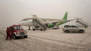 Indonesian airport personnel inspect volcanic ash covered planes and the airport of Yogyakarta