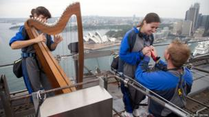 Lucas Farrell proposes marriage to his girlfriend Natalie Rumble as Irish-born harpist Cliona Molins plays a romantic tune at the top of the Sydney Harbour Bridge on Valentines Day