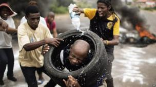 Protesters simulate a necklacing in Hebron, Pretoria, South Africa - Friday 7 February 2014
