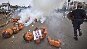 Baby sculptures strewn on a Nairobi street as police fire tear gas, Kenya - Thursday 13 February 2014