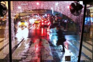 A New York City street on a cold, rainy evening as seen from the inside of an old commuter bus