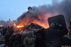 An anti-government protesters uses a slingshot during clashes with the police on Independence Square in Kiev early on February 19, 2014.