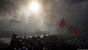 Interior Ministry members and riot police block a street as anti-government protesters gather in front of them amidst heavy smoke during clashes in Kiev