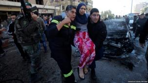 Civil defence members carry a wounded woman as a Lebanese Army soldier secures the area at the site of an explosion in the southern suburbs of Beirut