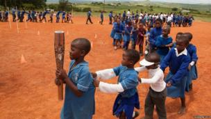 The Queen's Baton carried in a conga-like relay by the school children of the Ngwazini community, Swaziland.